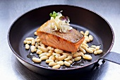 Fried salmon fillet with white beans in frying pan