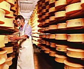 Man turning cheeses on wooden shelves