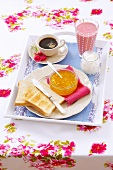 Toast, marmalade, quark, coffee and a strawberry smoothie on a breakfast tray