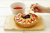 Brushing a fruit flan with cake glaze