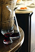 A glass of red wine and a carafe in a restaurant
