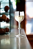 A glass of white wine on the bar in a pub