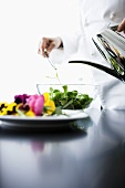 A chef pouring oil over a mixed leaf salad