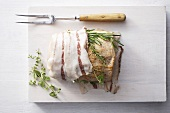 Preparing bacon and herb-wrapped loin of pork