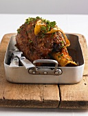 Veal shank with lemon in roasting tin