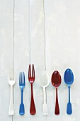Different coloured forks and spoons on wooden background