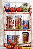 Fresh tomatoes in preserving jars and tins of tomatoes
