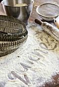 Schriftzug 'quiche' im Mehl und Backutensilien