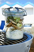 Mixed mushrooms in a creamy herb sauce in a preserving jar