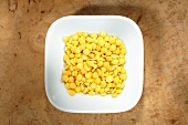 Yellow lentils in dish from above