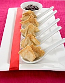 Wontons filled with surimi on spoons