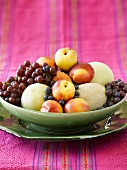 Melons, nectarines and grapes in fruit bowl