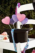 Heart-shaped lavender biscuits on sticks in a hat (Mad Hatter's Party)