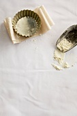 Tart tin, baking parchment and scoop with flour