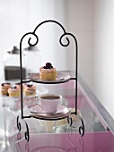 Cup of tea and cupcake on tiered stand