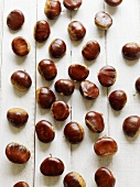 Chestnuts on white painted wooden background