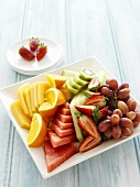 Plate of fruit: orange, melon, strawberries and grapes
