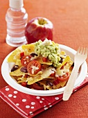 Nachos with vegetables and guacamole, apple, bottle of water