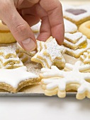 Hand taking Christmas biscuit from baking tray