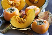 Japanese persimmons and pumpkin slices on autumnal leaves
