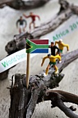 A miniature flag and toy football players on twigs