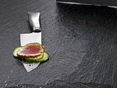 Santoku knife with slice of tuna and slices of vegetables