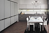 Edelstahl-Esstisch mit weißer Glasplatte und weiße Lederstühle unter Lüster in moderner Küche mit Einbauschrankwand