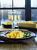 Macaroni and cheese with mangetout and glasses of white wine