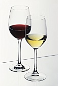 Glass of white wine in front of glass of red wine