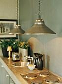 Küchenzeile mit Hängeleuchten über Herdplatten und runder Spüle in Beton-Arbeitsplatte