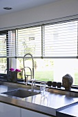 Küchenzeile mit Edelstahlspüle, Fensterfront und Jalousie