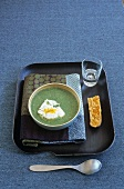 Cream of cress soup with poached egg and cheese croute on tray