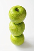 Three Granny Smith apples, one on top of the other