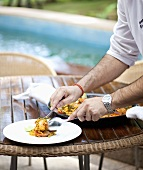 Paella being arranged on plates