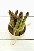 A bunch of green asparagus in a cup
