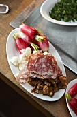An appetizer with salami and radishes