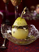 A poached pear with chocolate, gold leaf and pistachios