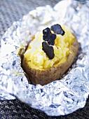 A jacket potato with black truffles