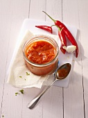Ajvar in a jar with red chilli peppers
