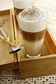 Two glass of latte macchicato in a wooden box