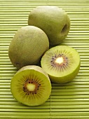 Chinese kiwis, whole and halved, on a bamboo mat