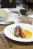 Duck breast with carrot puree in a restaurant
