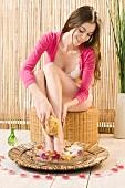 Frau wäscht ihre Beine im Blütenbad