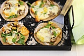 Mini pizzas with spinach, mushrooms and cheese