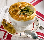 Chicken soup with smoked salmon, spinach and a puff pastry lid