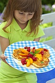 A girl holding a plate of pancakes and fresh fruit