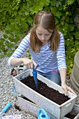 A girl making holes in soil for seeds