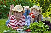 Zwei Mädchen auf Wiese liegend mit Tomaten, Salat & Gurken