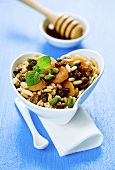 Muesli with dried fruit and honey in a heart-shaped bowl