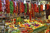 A market stall with chilli peppers, garlic, fruit and vegetables (Mercat de St. Josep (Boqueria), Las Ramblas, Barcelona, Spain)